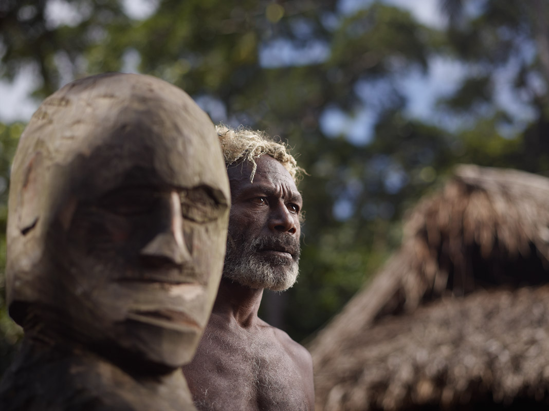 Chief Mangau beside wooden head carving. A club is used to beat the statue in order to call the entire village for meetings. Yakel, Tanna Island, Vanuatu