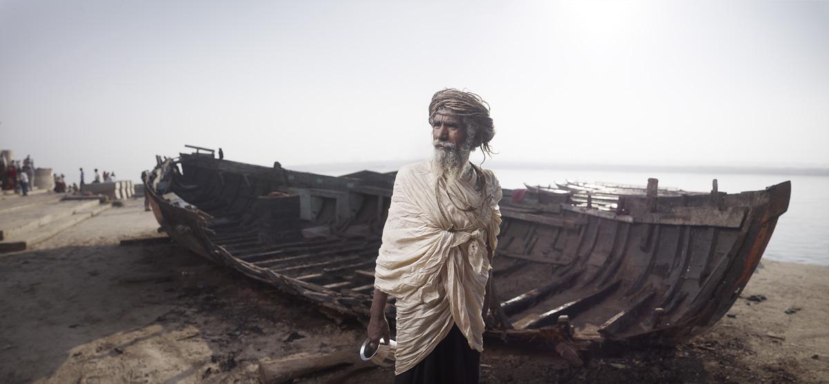 Ram Das beside boat wreckage in Varanasi, India.