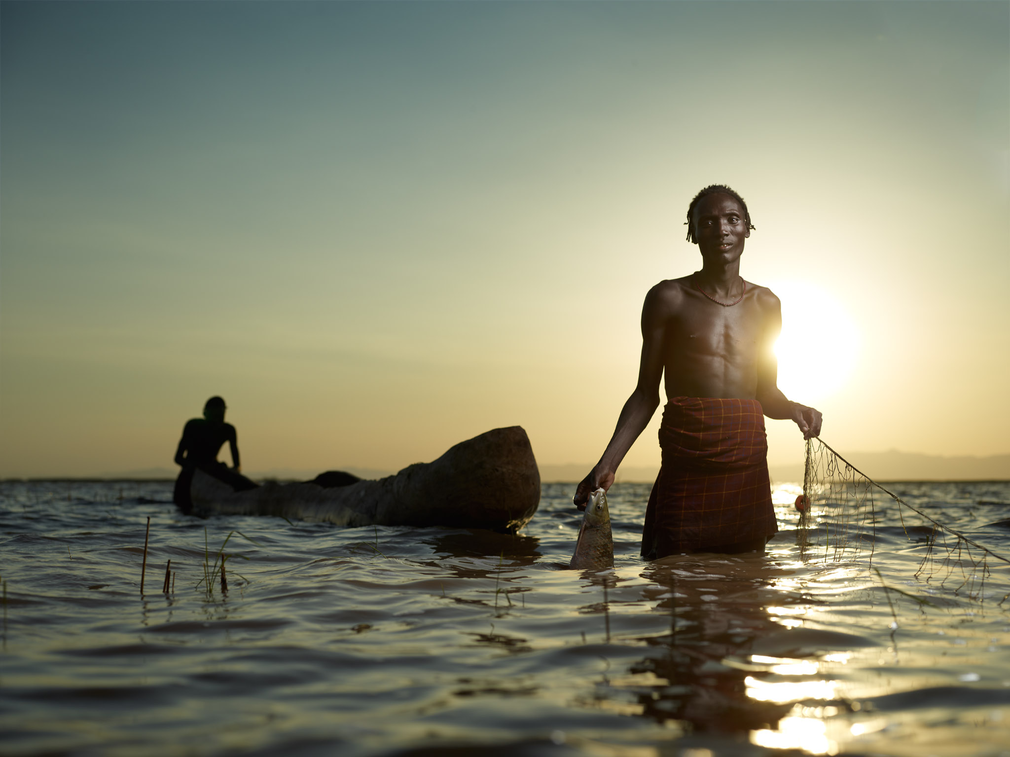 Shallowgo checks his fishing nets for the daily catch. The Omo River's flow is essential to the health of the lake, channeling fresh water via great deltas. In recent times, the Dassanach have seen the lake retreat, shrinking in size and increasing in salinity. Dassanach tribe, Ethiopia.