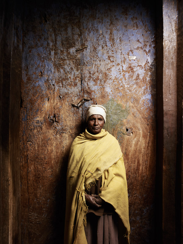 Mother Harya, a nun of Abraham Atsbeha. She poses against the ancient doors of a former Pagan church, which has been converted to an Orthodox Christian place of worship. Only on one day of the year, the stone pillars inside leak holy water.