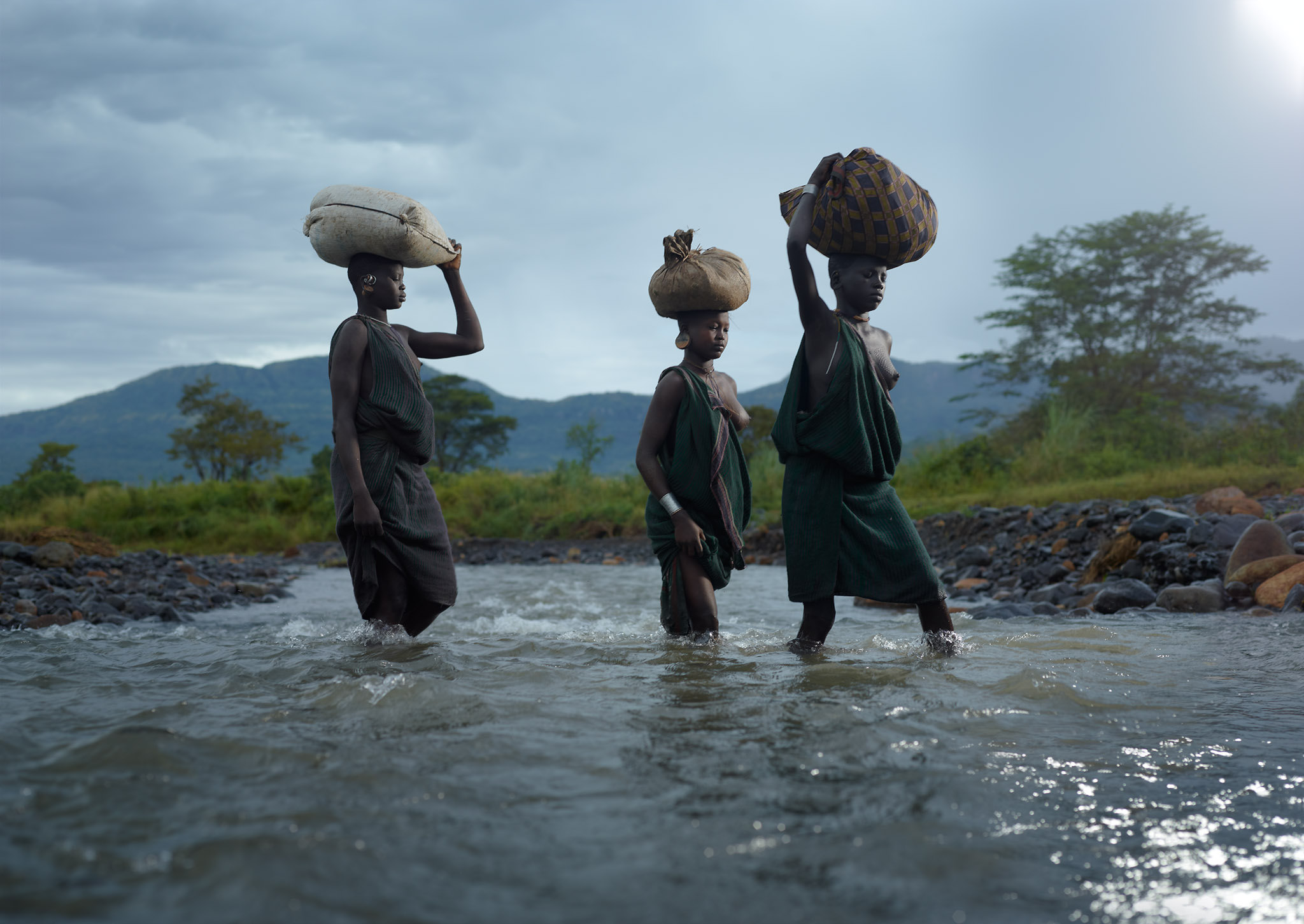 Surma women Naguio, Nabelgoo and Nakoguinea cross Kibbish River. Suri Tribe Territory, Lower Omo Valley, Ethiopia