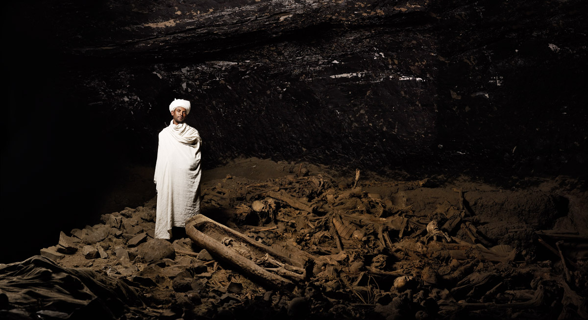 """Keas Hable Mariyam, the monk of the cavern church, poses on top of an estimated 5740 remaining pilgrim corpses. """"Most of them came from Jerusalem and now they remain here to rest."""" Lalibela, Ethiopia"""