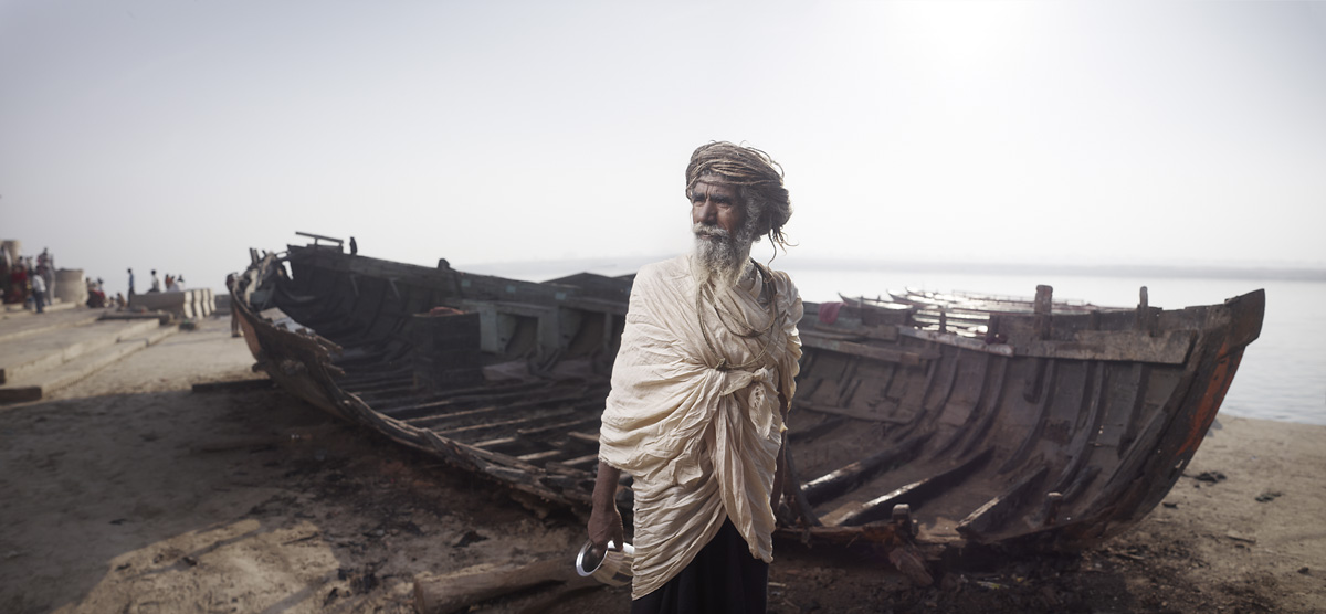Ram Das beside boat wreckage in Varanasi, India.